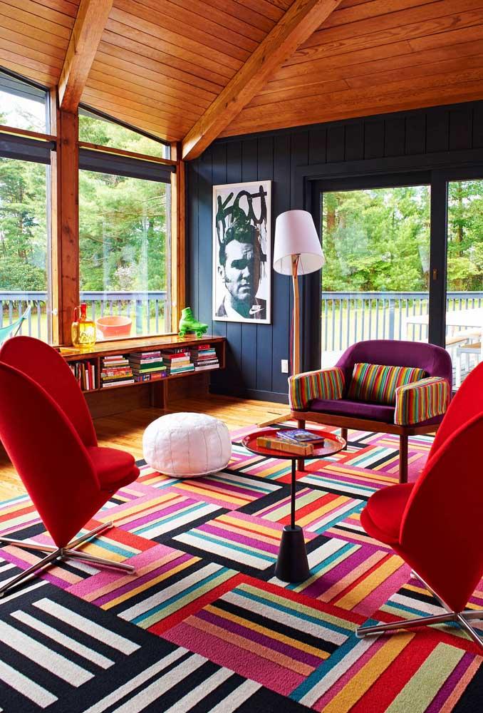 Nessa sala de estar iluminada, a opção foi por uma decor ousada e marcante a partir do uso das poltronas coloridas e do tapete listrado