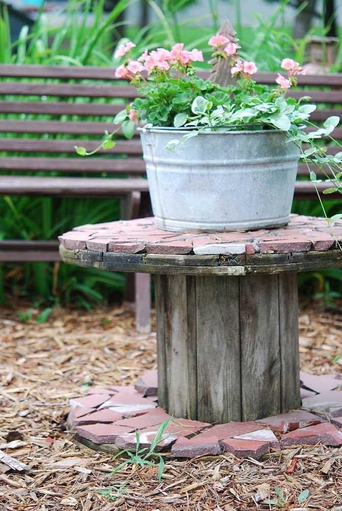 No jardim, a bobina de madeira ganhou um mosaico rústico e se tornou perfeita para abrigar as plantinhas