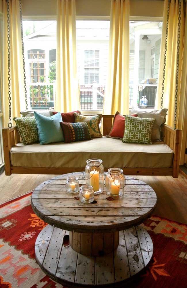 Essa sala original, de sofá suspenso, apostou em uma mesa de carretel para completar a decor