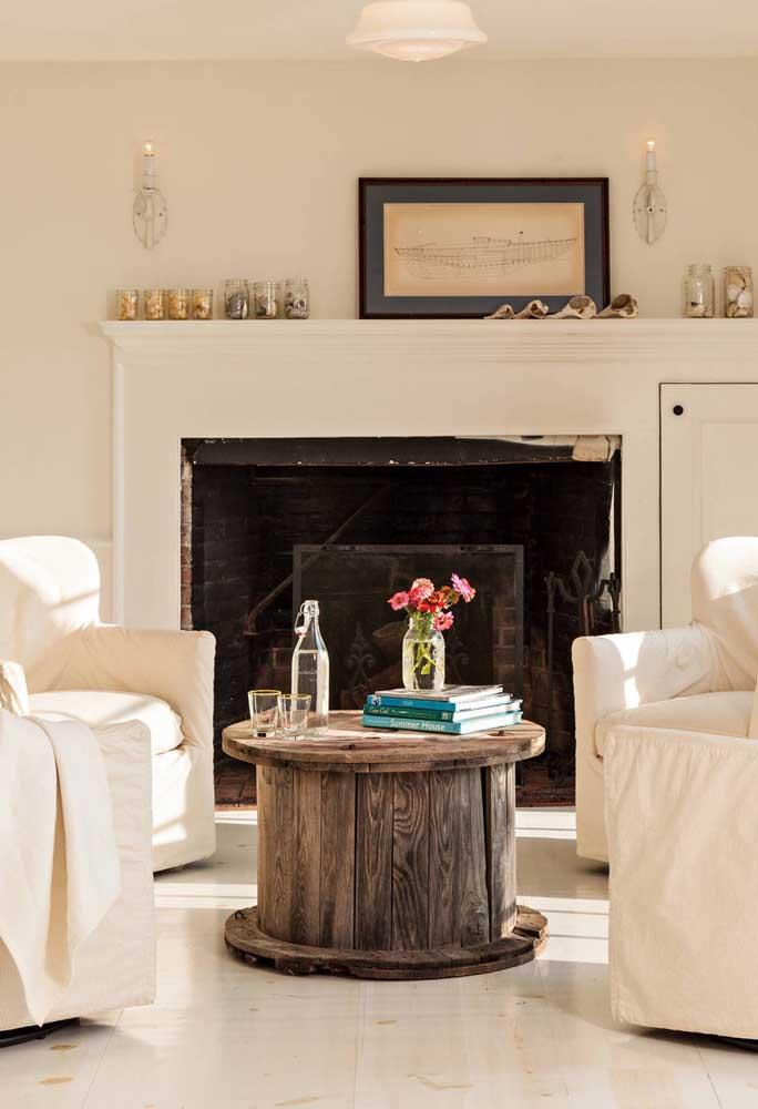 Nessa sala clean e bem iluminada, a mesa rústica de carretel forma uma linda dupla com a lareira aos fundos