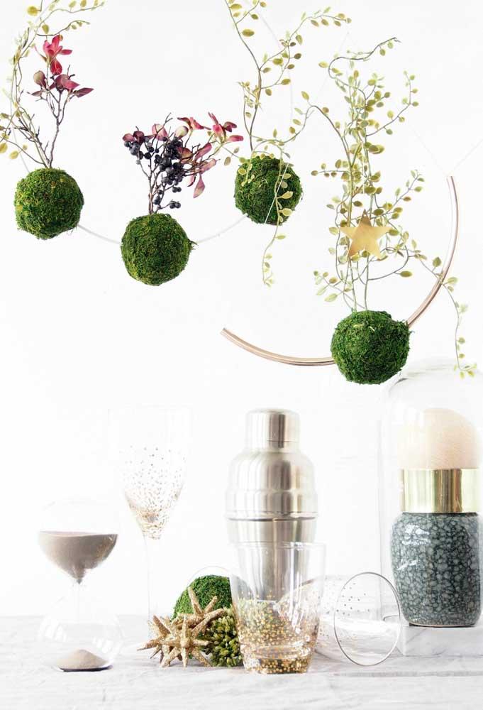 Linda composição de kokedamas suspensas; destaque para o musgo verde e brilhante envolvendo os arranjos