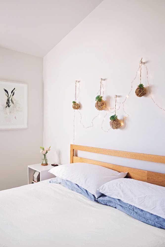 Quarto clean e delicado decorado com kokedamas junto à parede da cabeceira