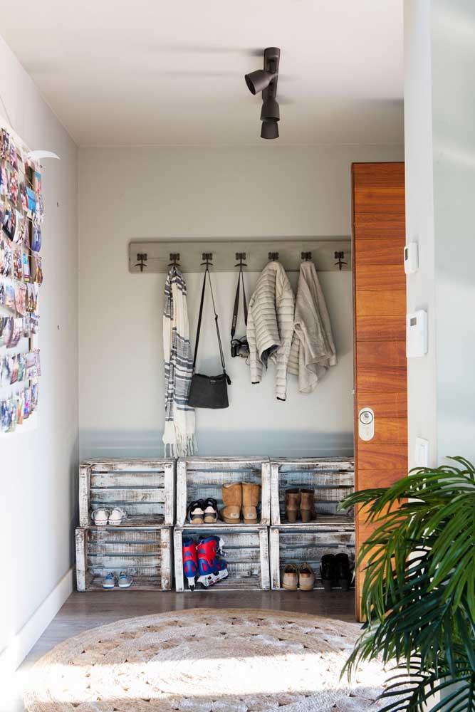 No hall de entrada, os caixotes de madeira se transformam em uma sapateira sustentável