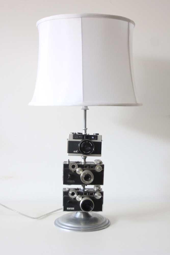 Para formar o abajur irreverente, as câmeras antigas foram usadas junto à base de ferro