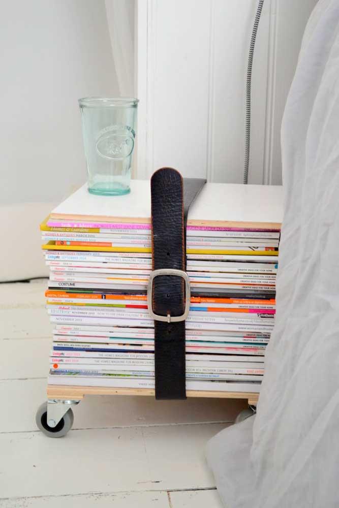 Uma pilha de revistas antigas forma a mesa lateral do quarto; repare que as peças foram sustentadas pelo cinto