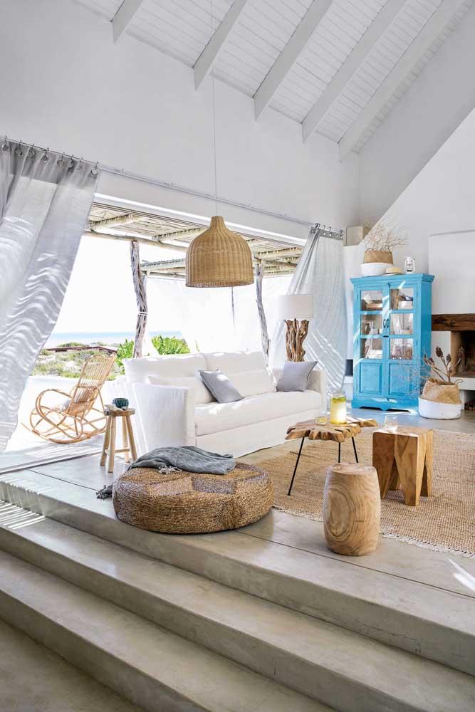 A sala de estar da casa de praia ganhou a companhia de móveis reciclados para compor o ambiente