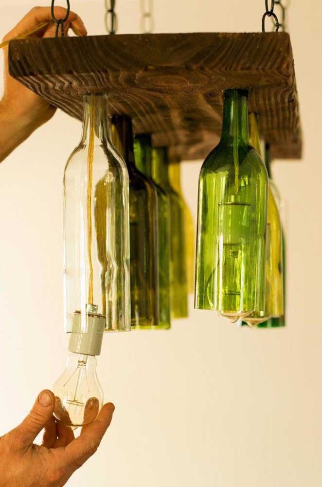 Aqui, as garrafas velhas tiveram suas bases recortadas e foram acopladas a uma placa de madeira. Com isso, foi possível instalar a fiação para fazer uma linda luminária