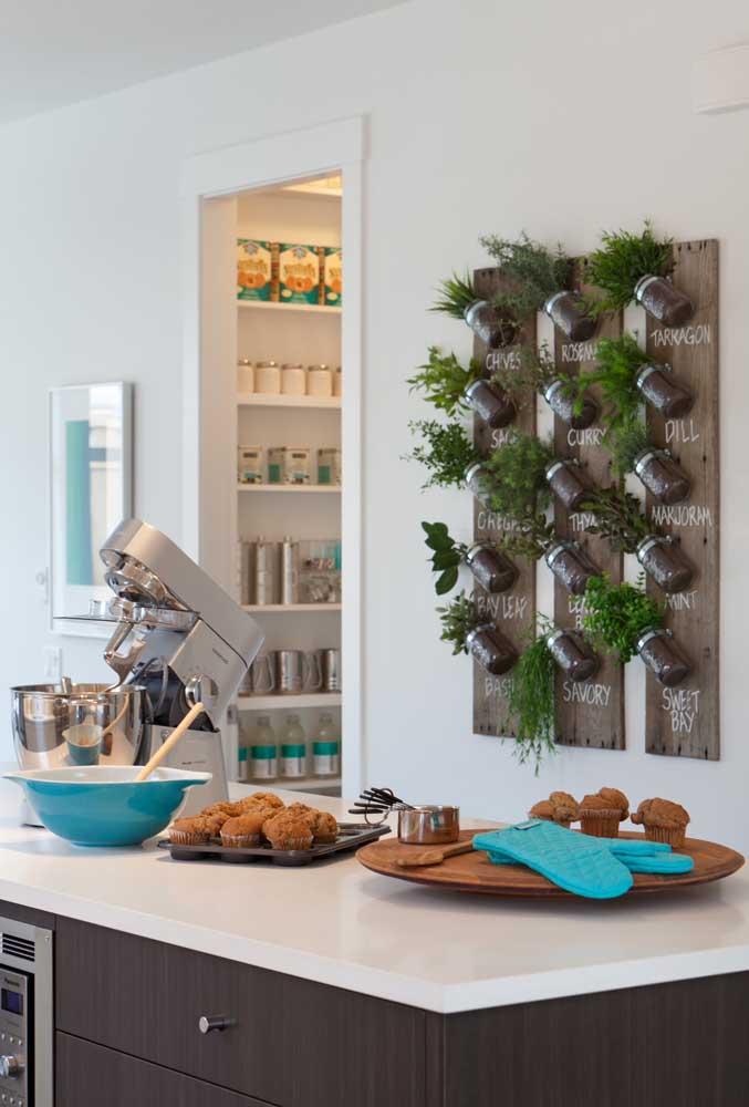 Horta vertical feita com placas de madeira e potes de vidro no lugar dos vasos