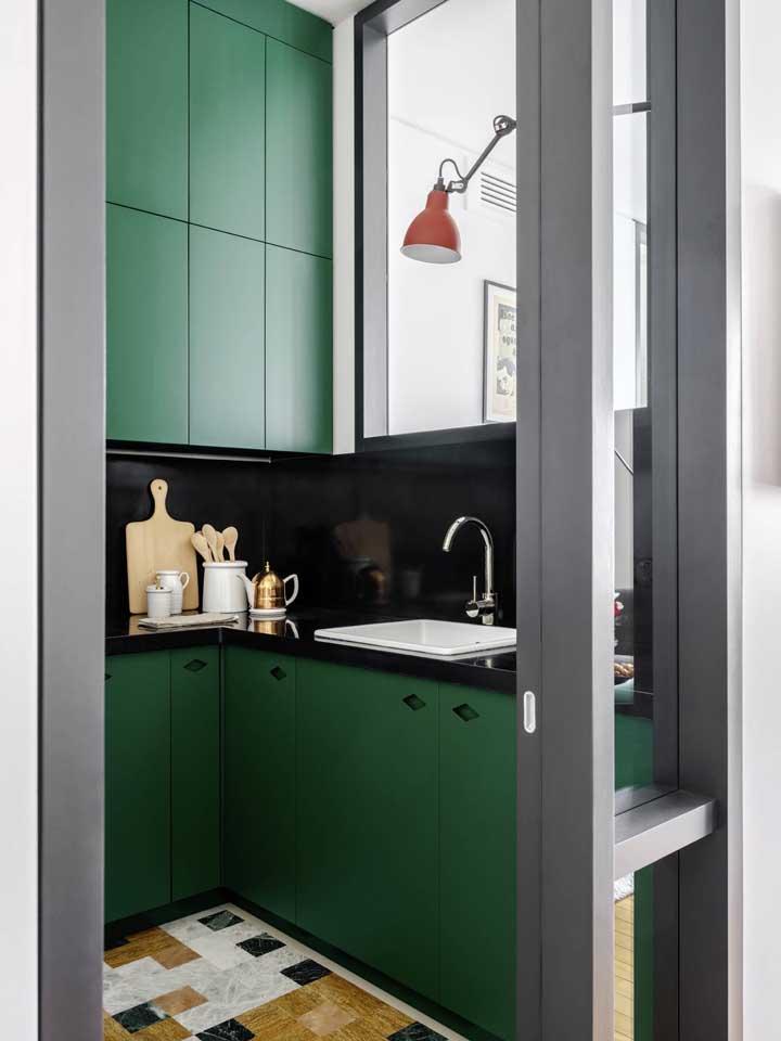 Linda inspiração de cozinha com armários verdes e bancada de granito preta; destaque para o piso em tons de preto e amarelo contrastando com o móvel
