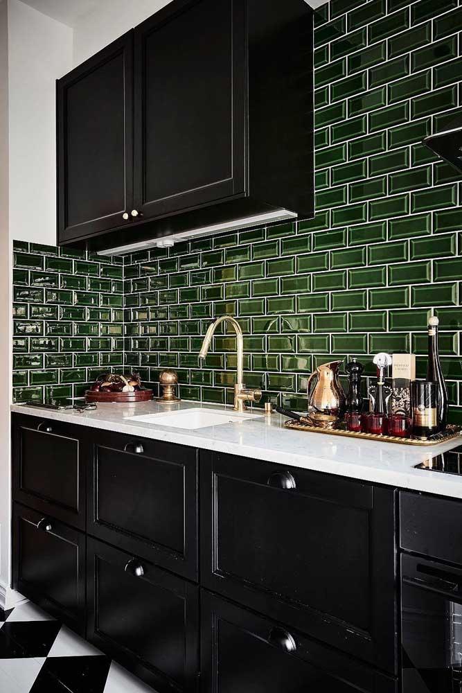 Azulejos de metro verde em contraste harmonioso com os móveis pretos da cozinha