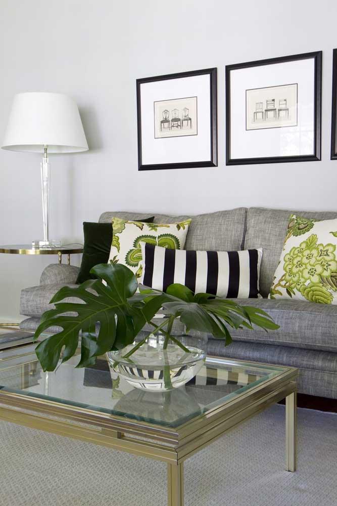Tons de verde nos detalhes da decoração dessa sala de base branca e preta