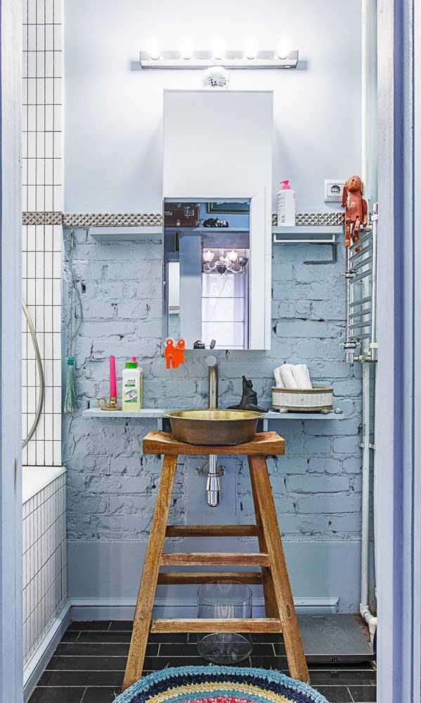 Esse banheiro moderninho não teve problemas com a parede desgastada revelando os tijolos usados na construção, nem com o suporte para pia feito com um banco de madeira