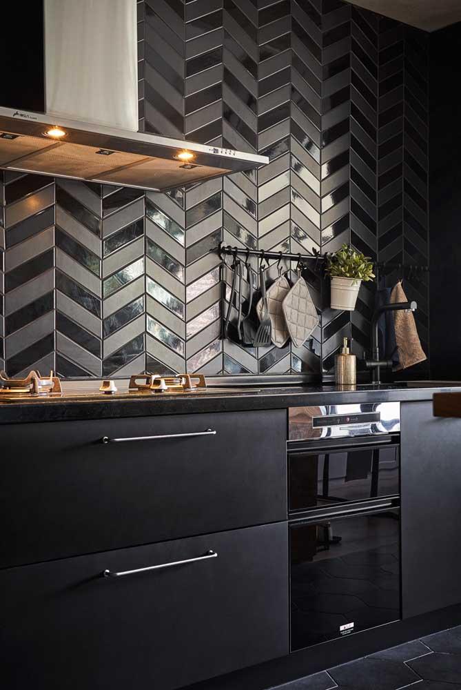 Linda, linda, linda! Essa cozinha com subway tiles nas cores preto e cinza ganhou uma paginação espinha de peixe deslumbrante
