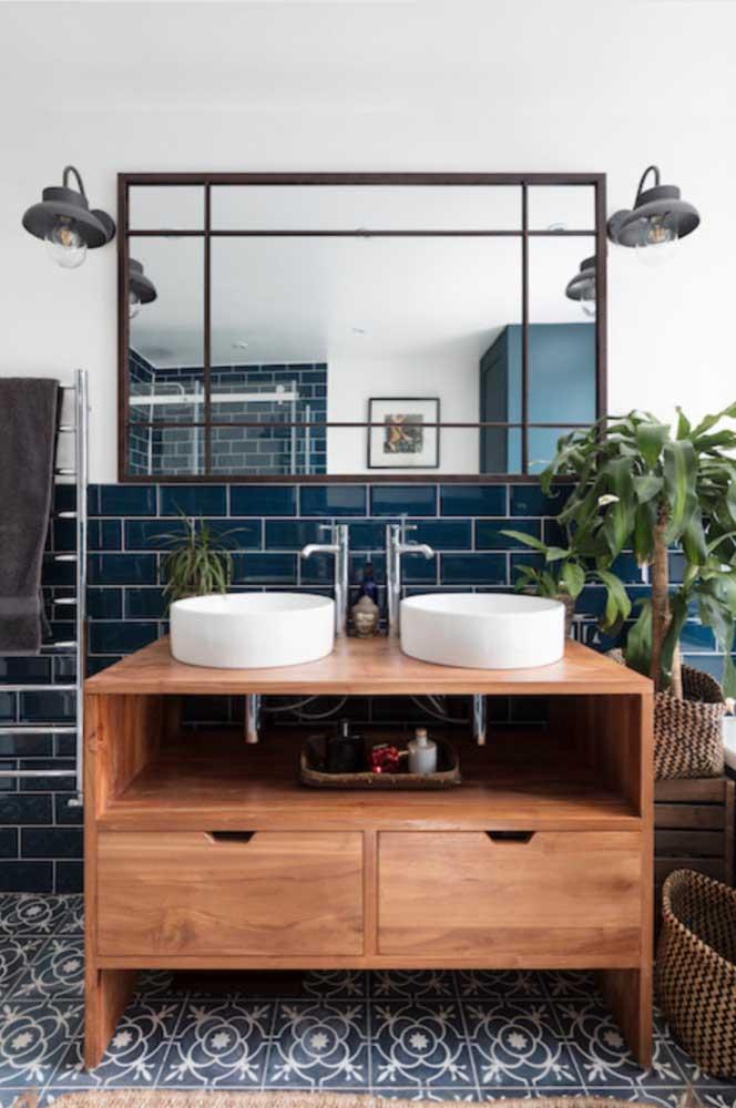 Super charmoso e elegante esses subway tiles azul escuro; o tom do revestimento casou muito bem também com o piso e o móvel de madeira