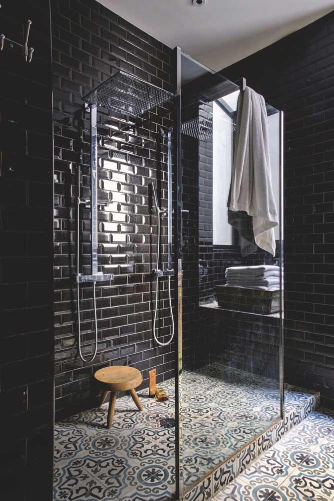 Um banheiro pra lá de moderno e sofisticado com subway tiles na cor preta e ladrilhos hidráulicos no chão