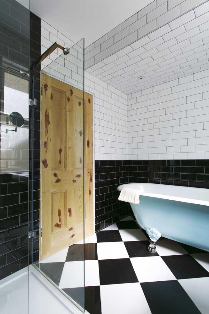O clássico preto e branco marcam presença nesse banheiro com os subway tile e o piso de cerâmica; para quebrar a dualidade, uma banheira azul claro