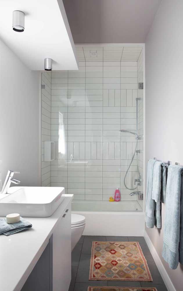 Banheiro simples com subway tiles no interior do box; destaque para a paginação criativa feita com o revestimento