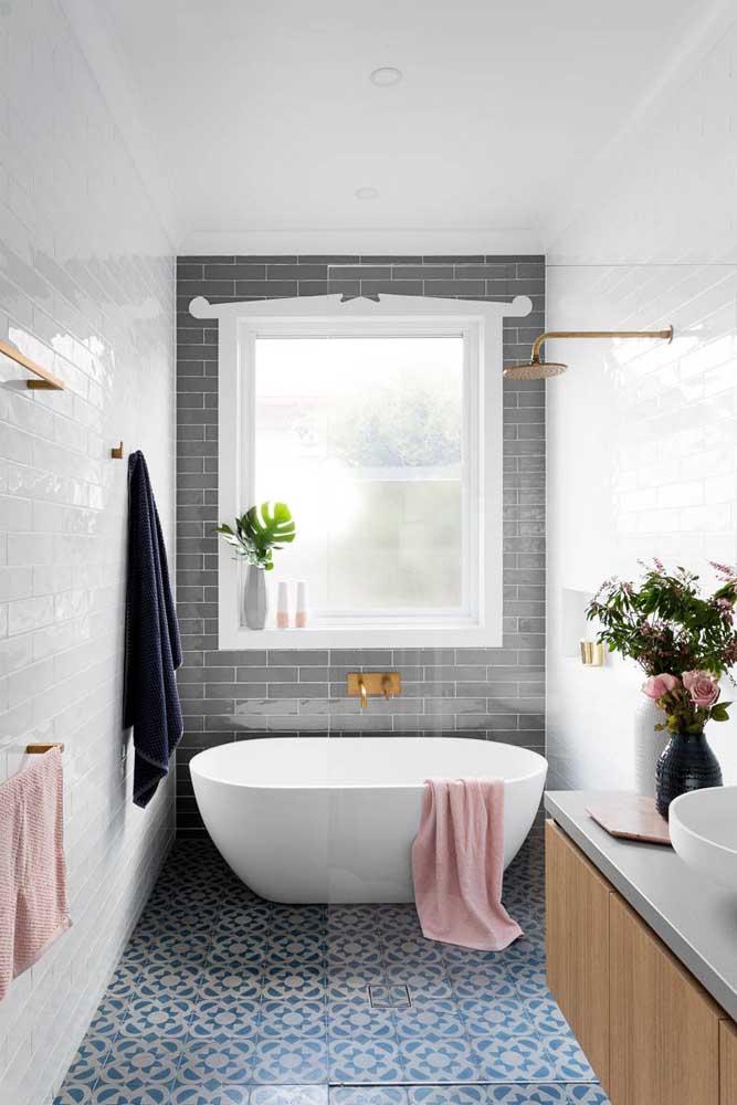 Esse banheiro cheio de estilo próprio optou pelo uso de duas cores de subway tiles e uma paginação que parece estar incompleta