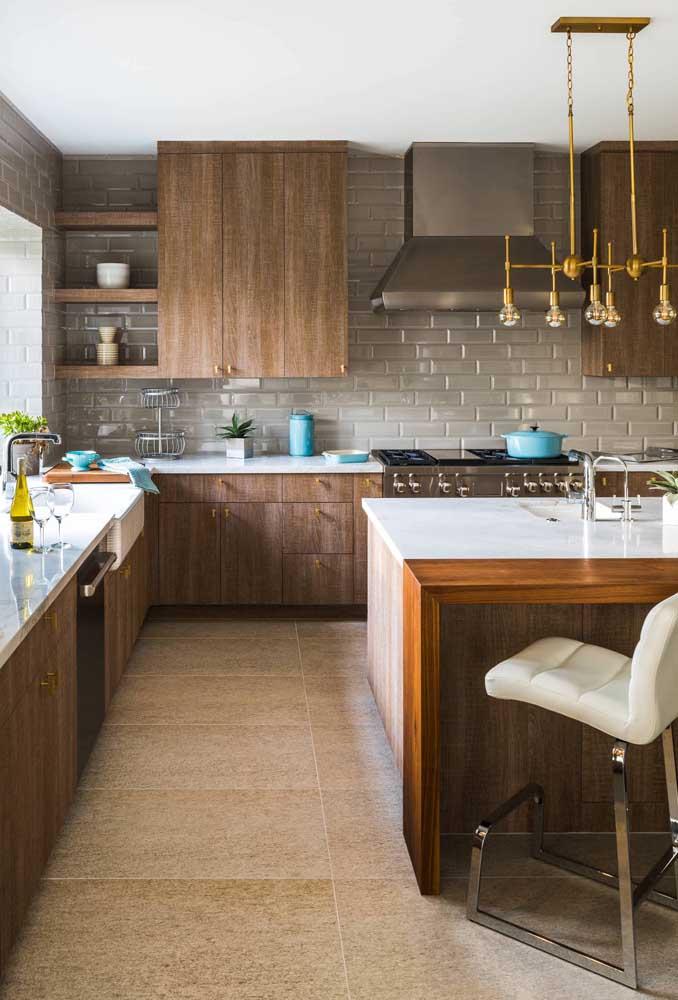 O tom cinza do subway tile casou perfeitamente com os móveis em madeira da cozinha