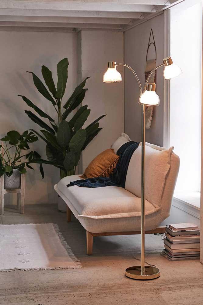 O lugar mais tradicional para um abajur de chão: ao lado do sofá; esse modelo charmoso conta com três lâmpadas