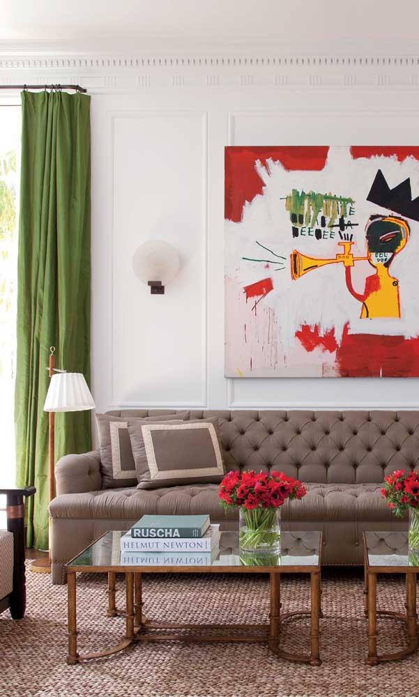 Abajur de chão pequeno e discreto ao lado do sofá; pela altura, ele tem caráter decorativo e de luz difusa, apenas