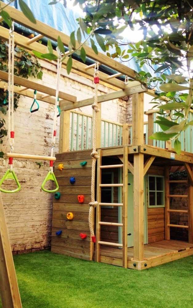 O quintal pequeno ganhou uma casinha de madeira com parede de escalada, mezanino e trepa trepa