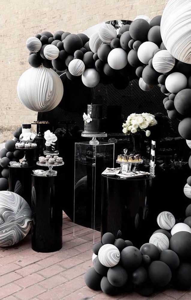 Um arco de bexiga super moderno para a mesa do bolo nas cores preto e cinza