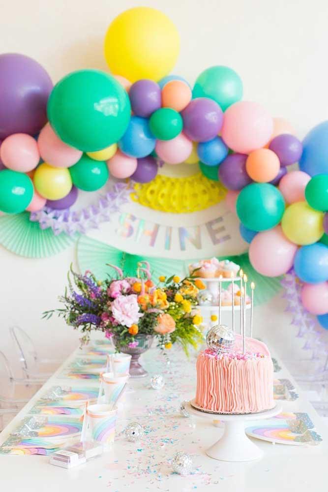 Mesa de aniversário com arco de bexiga colorida ao fundo