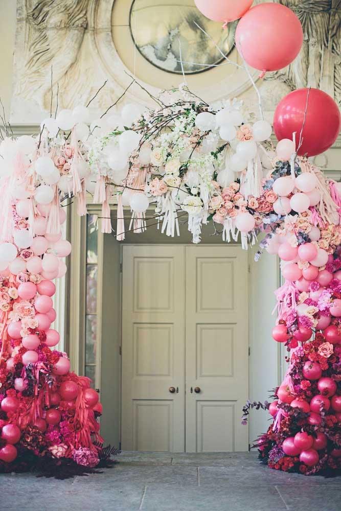 A entrada dessa festa ganhou um arco de bexiga elegante, decorado com galhos e balões flutuantes