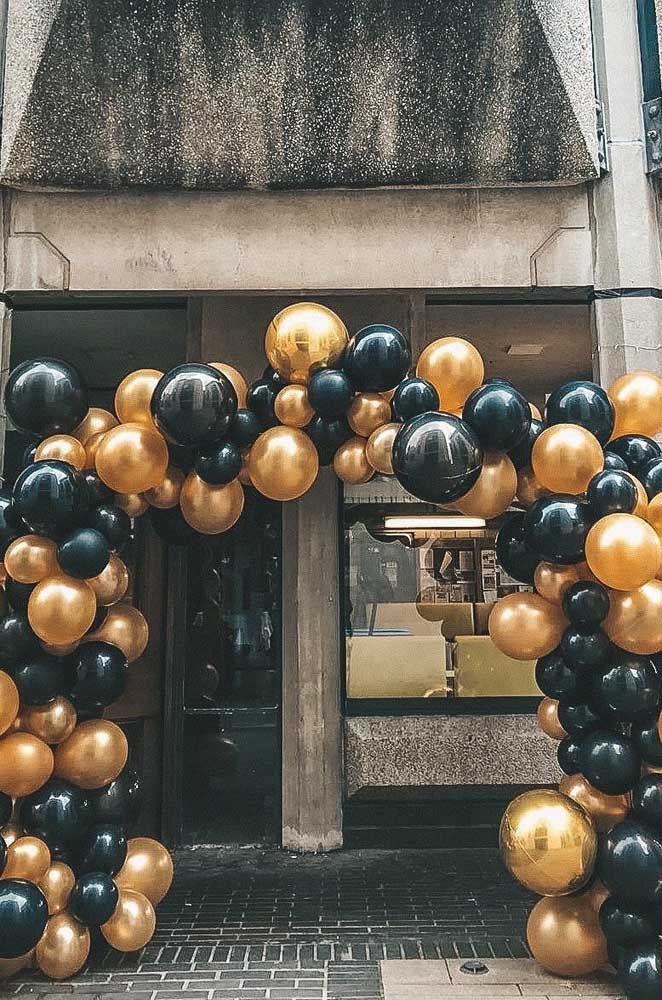 Arco de bexiga para entrada da festa feito com balões dourados e pretos
