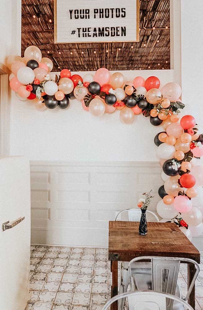 Arco de bexiga desconstruído e decorado com flores e folhas, ideal para festas de casamento