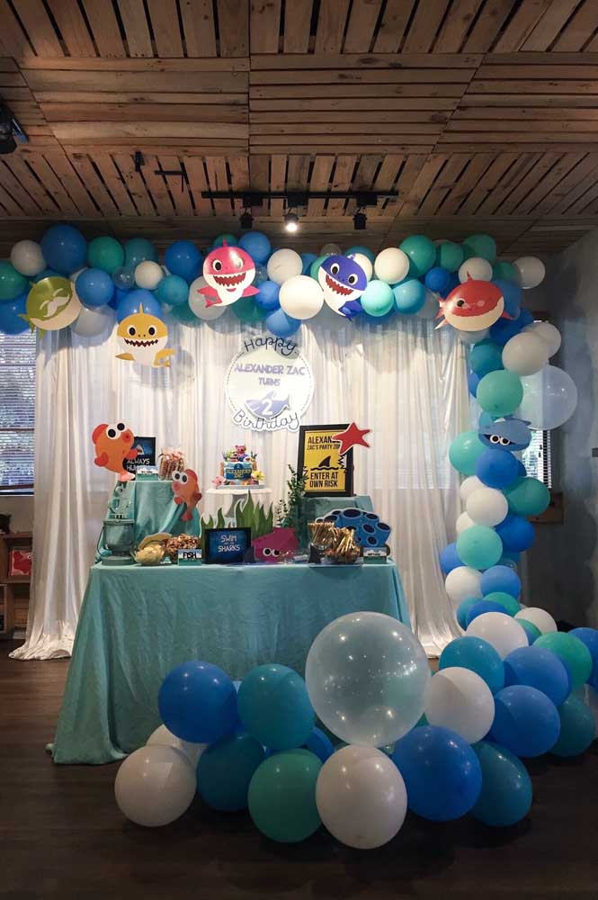 Festa infantil temática com arco de bexiga que se estende até a frente da mesa