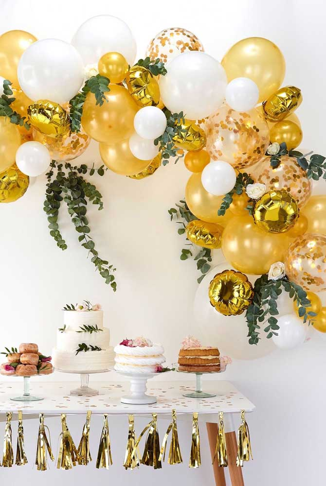 A decoração da festa de casamento se valorizou com o arco desconstruído feito de balões metalizados dourados