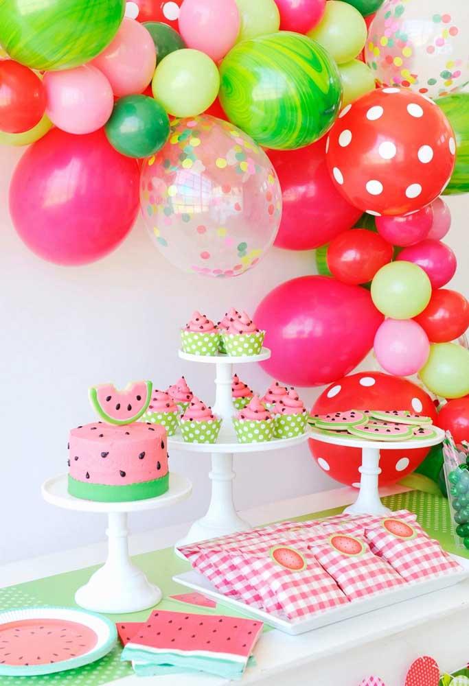 A festa com tema de melancia trouxe um arco de bexigas nos mesmos tons da mesa