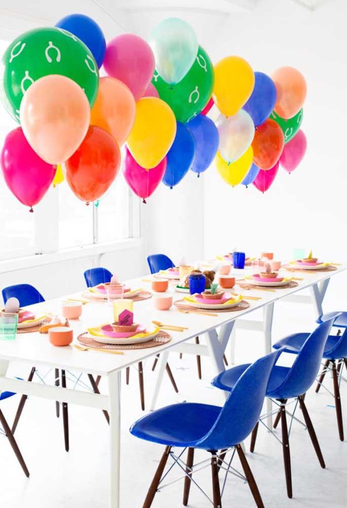 Para enfeitar a mesa principal, use balões coloridos suspensos em cima da mesa. Mais colorido, impossível!