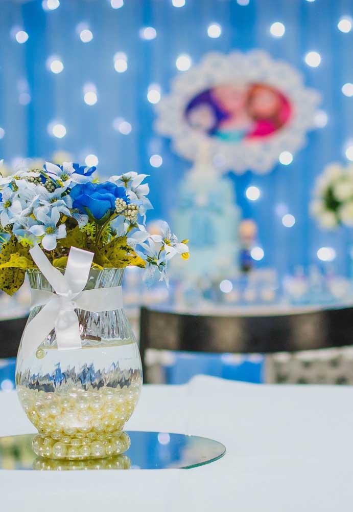 Centro de mesa para festa Frozen feito com flores azuis combinando com as cores do tema