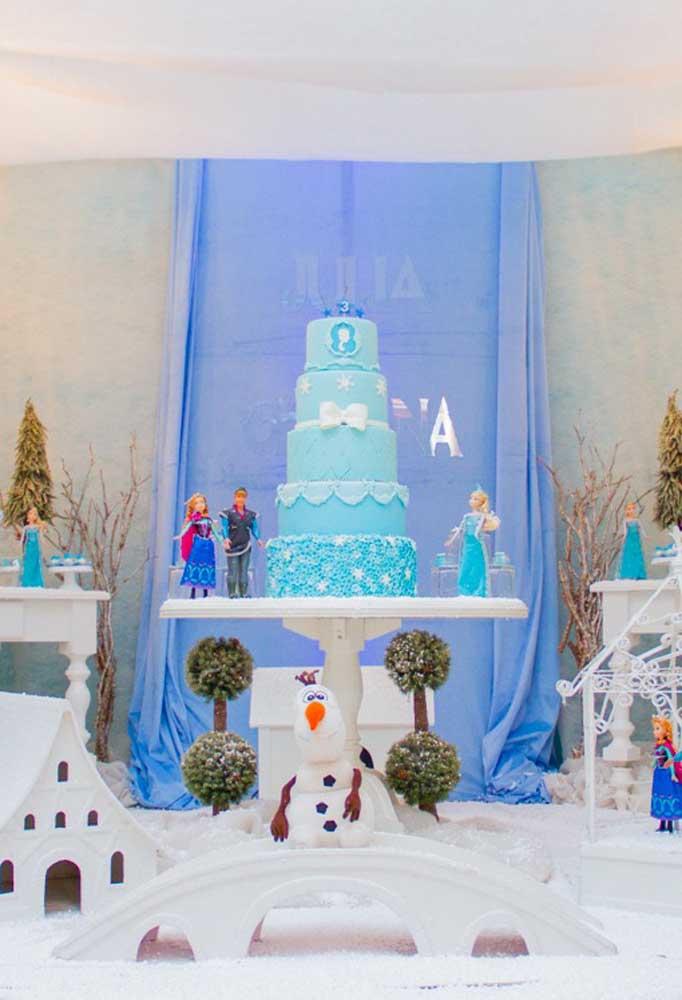Festa Frozen decorada com bonecos dos personagens. Repare que o fundo simples foi feito usando apenas tecido