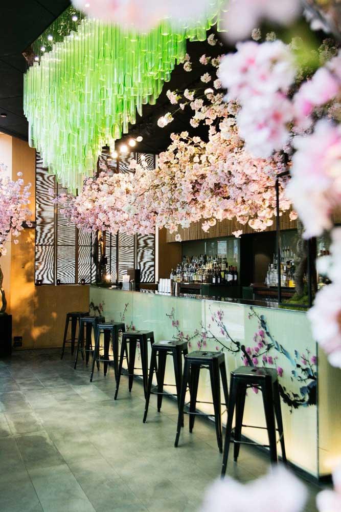 Um bar delicadamente decorado com flores de cerejeira suspensas e também no balcão