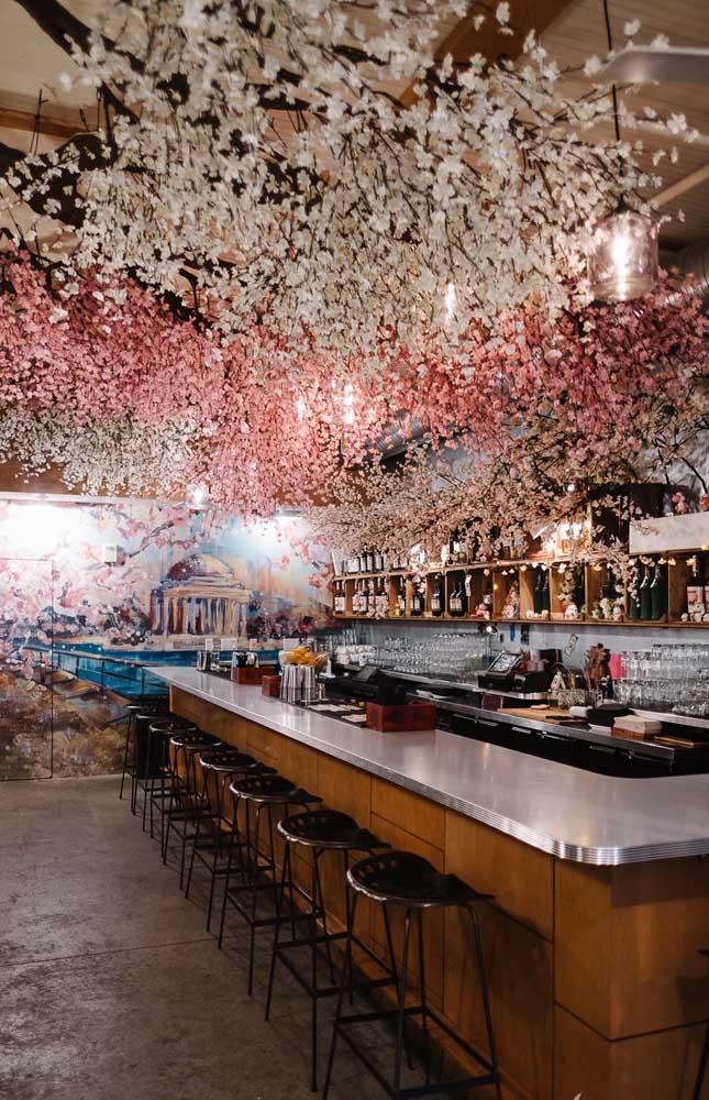 Cerejeiras brancas e rosas decoram o teto desse bar; linda opção de decoração para uma festa de casamento, por exemplo