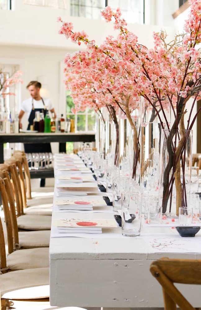 Um espetáculo de mesa de casamento decorada com vasos altos de flores de cerejeira