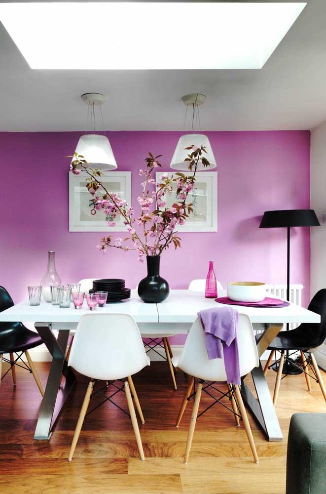 Sala de jantar decorada com arranjo de flor de cerejeira, formando uma linda combinação com a parede de tom similar