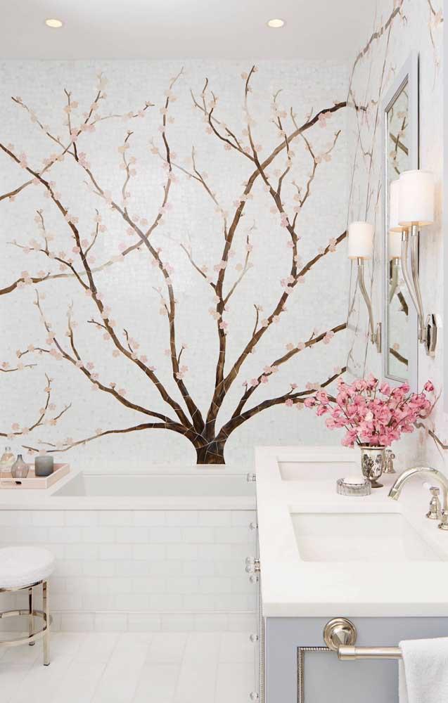 O banheiro branco ganhou um lindo destaque com o painel de flores de cerejeira; repare que as flores também estão sobre a bancada