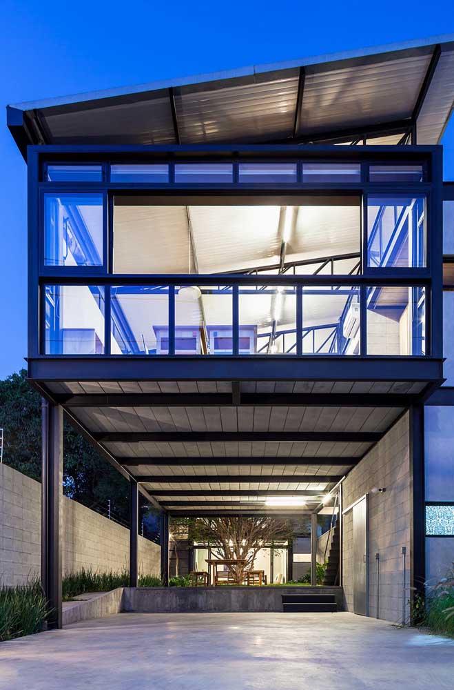 Vista para a garagem e fachada da residência em Steel Frame com design industrial