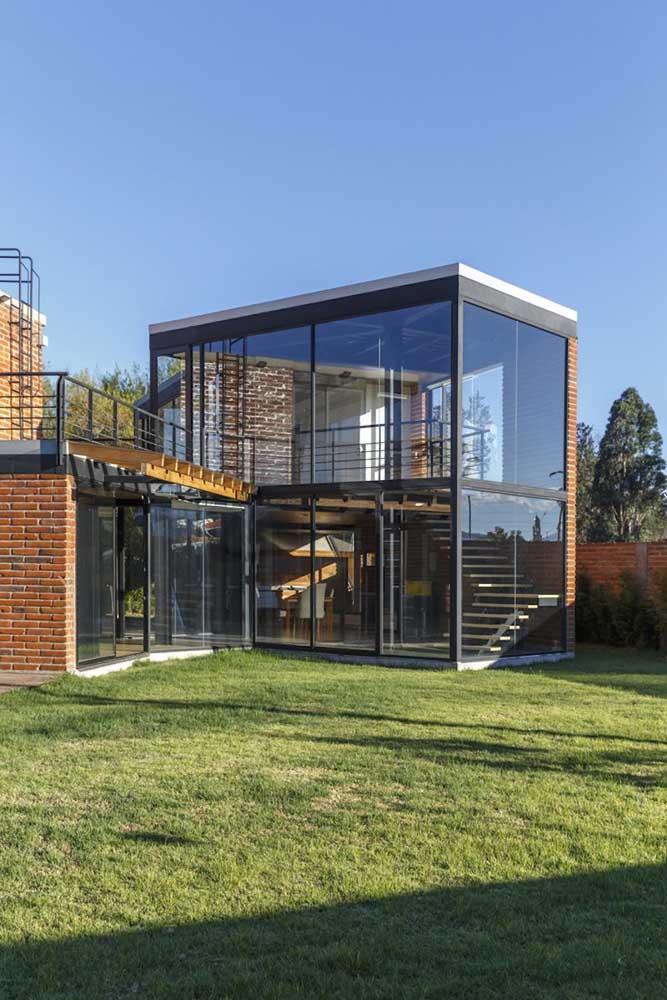 Casa contemporânea em Steel Frame com tijolo à vista ornando com as paredes em vidro
