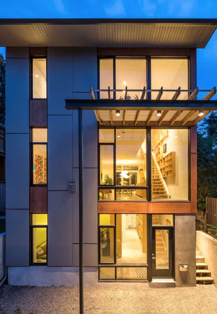 O pé direito duplo da residência fica aparente com as grandes janelas de vidro da construção em Steel Frame