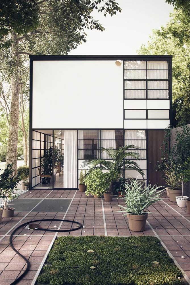 Fachada de uma casa cheia de estilo, com estrutura em Steel Frame e jardim na entrada