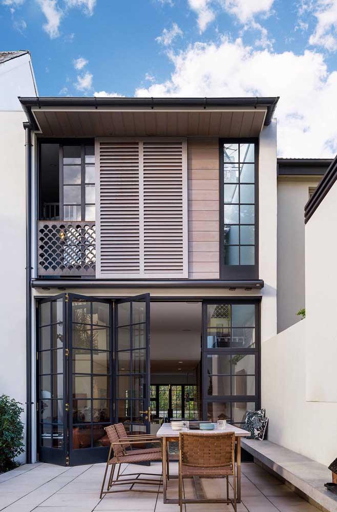 Inspiração aconchegante de casa em Steel Frame, com portas de vidro e varanda aberta