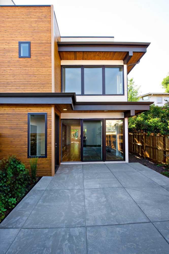 Entrada da casa em Steel Frame, com acabamento em madeira e porta de vidro de correr