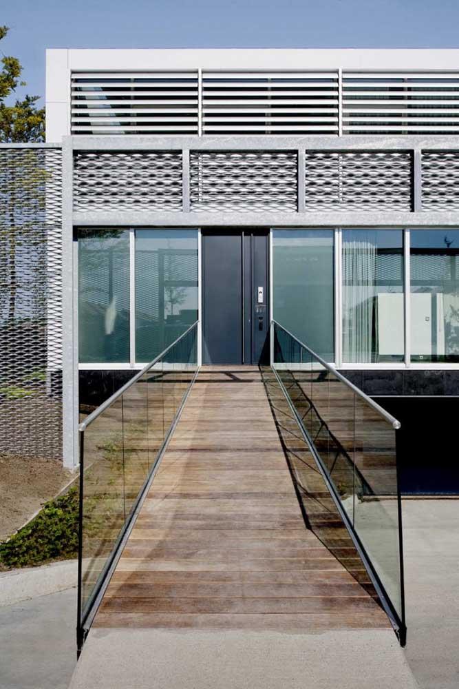 A entrada dessa casa em Steel Frame ganhou uma rampa com acabamento em madeira e vidro