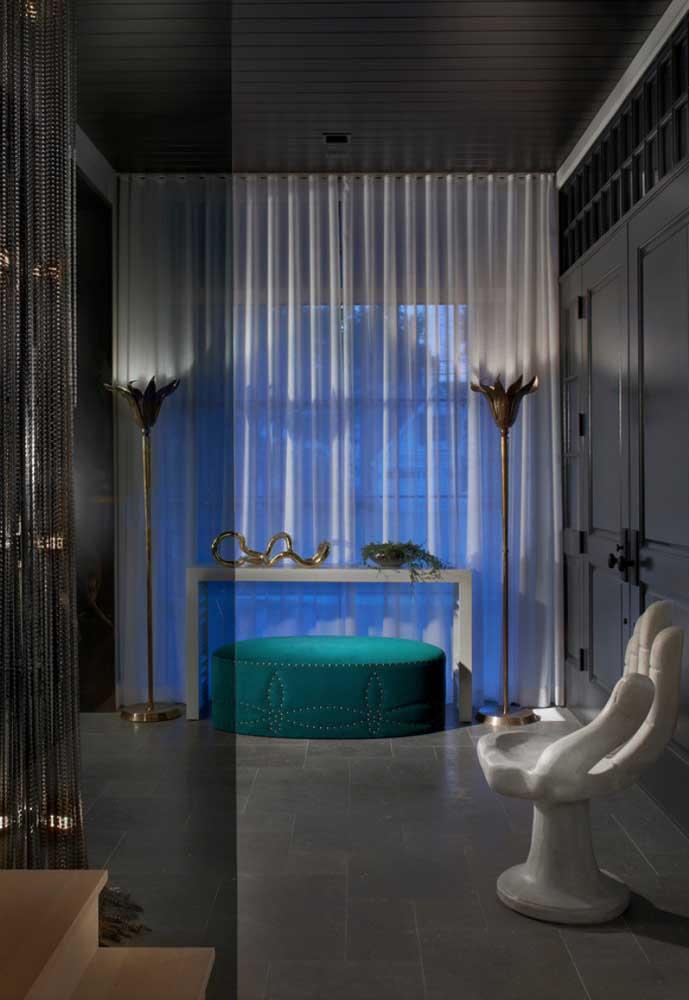 A iluminação azul na parede ajuda a destacar a cortina de voil branco